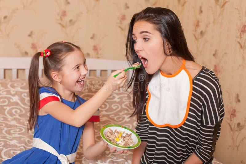 小女孩喂养她的从匙子的母亲 库存照片