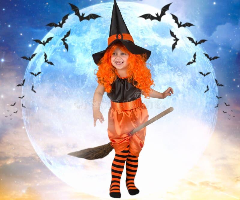 小女孩在一把笤帚的巫婆飞行横跨天空 免版税库存图片