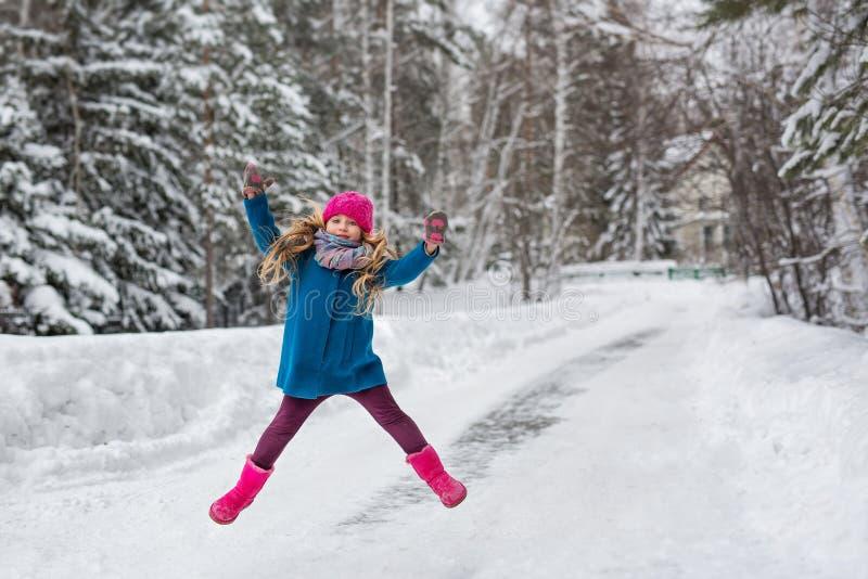 小女孩在一件蓝色外套和一个桃红色帽子和起动,跳高冬天森林穿戴了 免版税库存照片