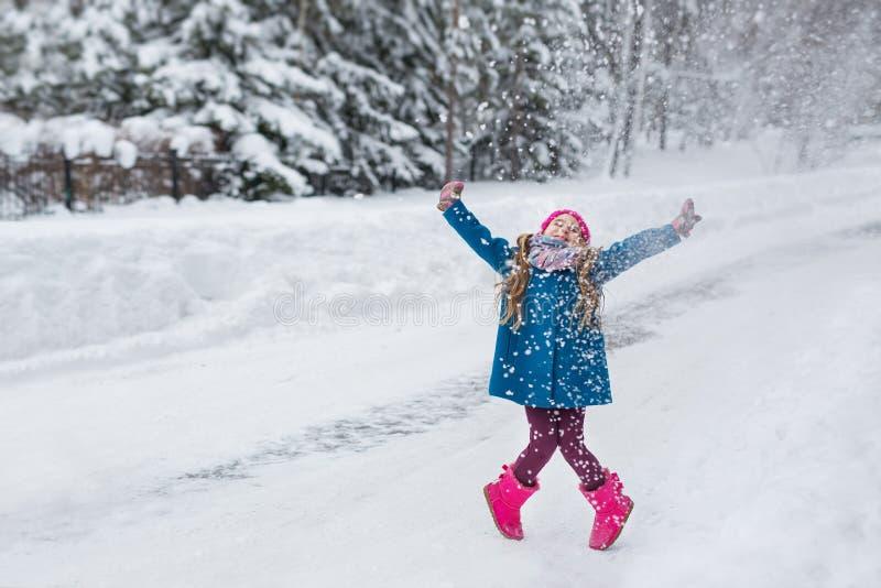 小女孩在一件蓝色外套穿戴了和一个桃红色帽子和起动,海明和使用在冬天森林里 库存照片