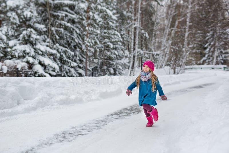 小女孩在一件蓝色外套穿戴了,并且一个桃红色帽子和起动,乐趣通过冬天森林运行 免版税库存照片