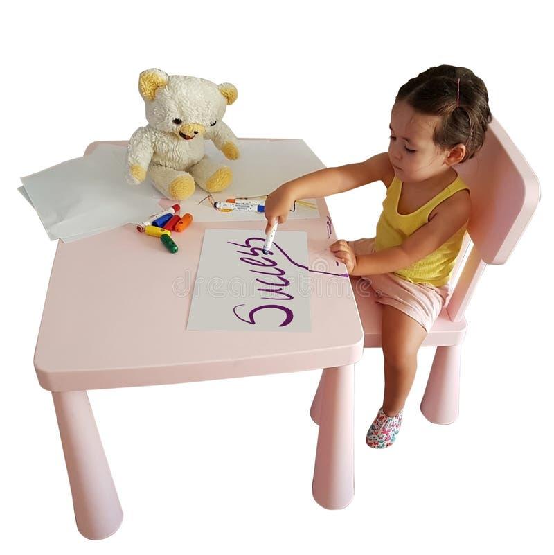 小女孩在与被隔绝的玩具的纸写成功 免版税库存照片