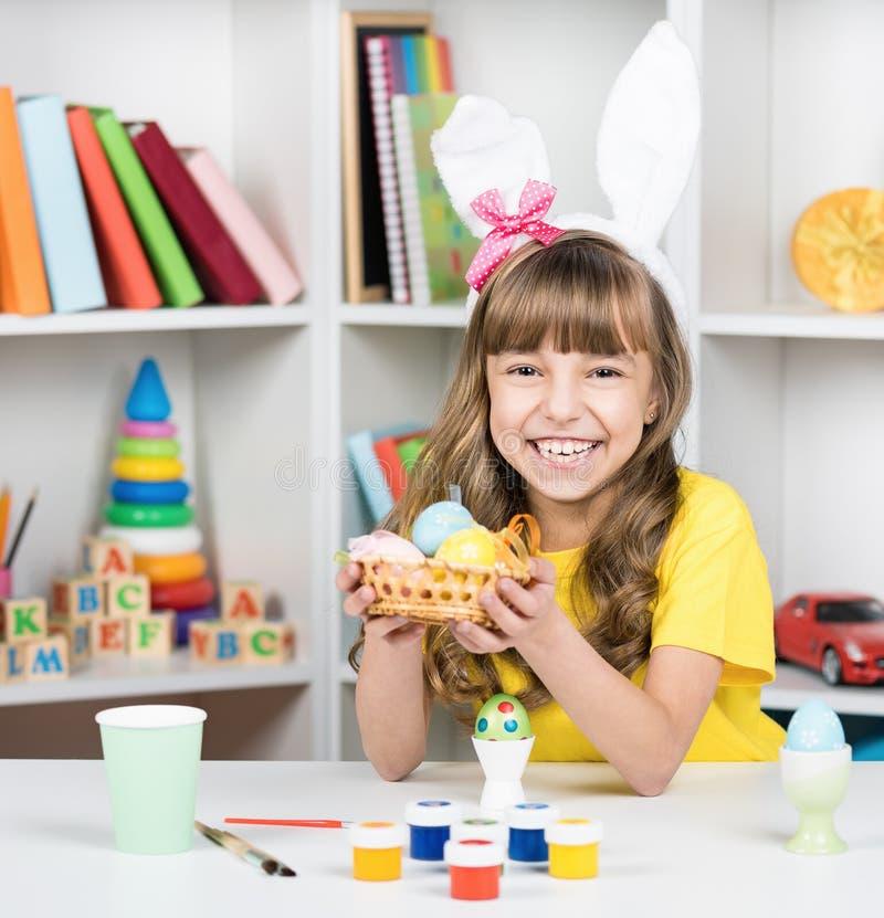 小女孩在兔宝宝耳朵穿戴了用复活节彩蛋 图库摄影