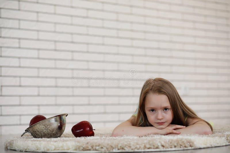 小女孩在地板上说谎 免版税库存图片