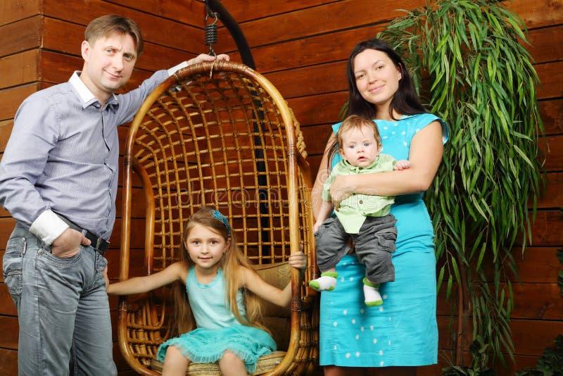 小女孩在垂悬的椅子和父亲,有婴孩的母亲坐 免版税图库摄影