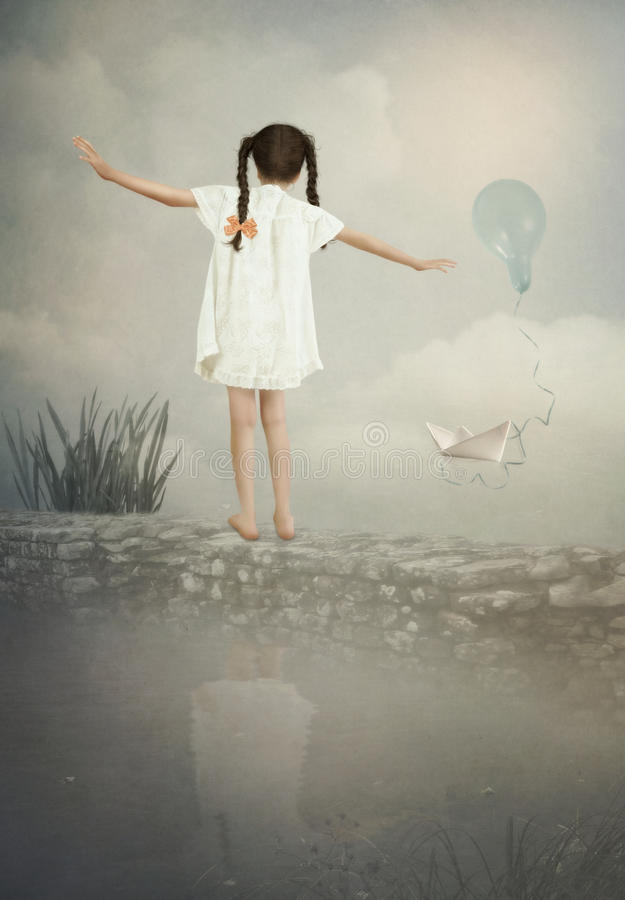 小女孩在墙壁上平衡 免版税库存照片