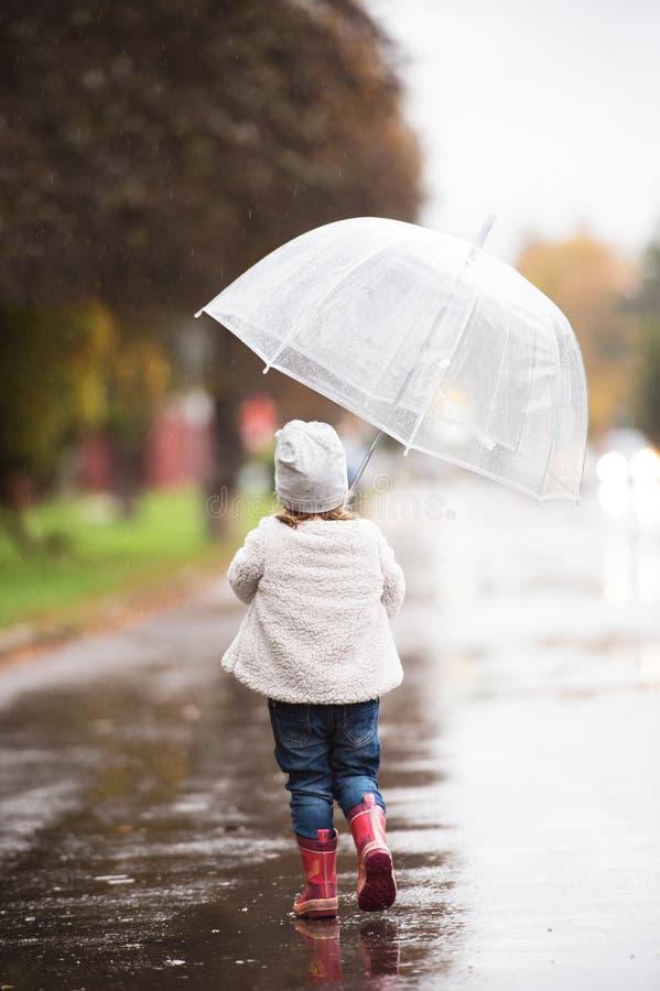 小女孩在外面透明伞下,雨天 免版税库存图片