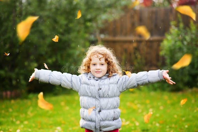 小女孩在天空中投掷秋叶 图库摄影