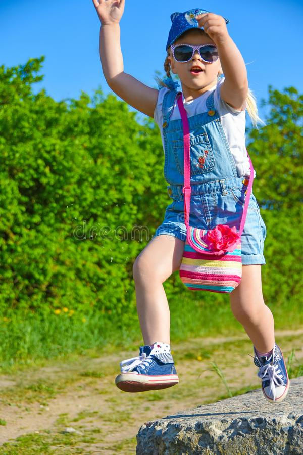 小女孩在她的手上使用与一朵花,跳从高度,微笑 免版税库存图片