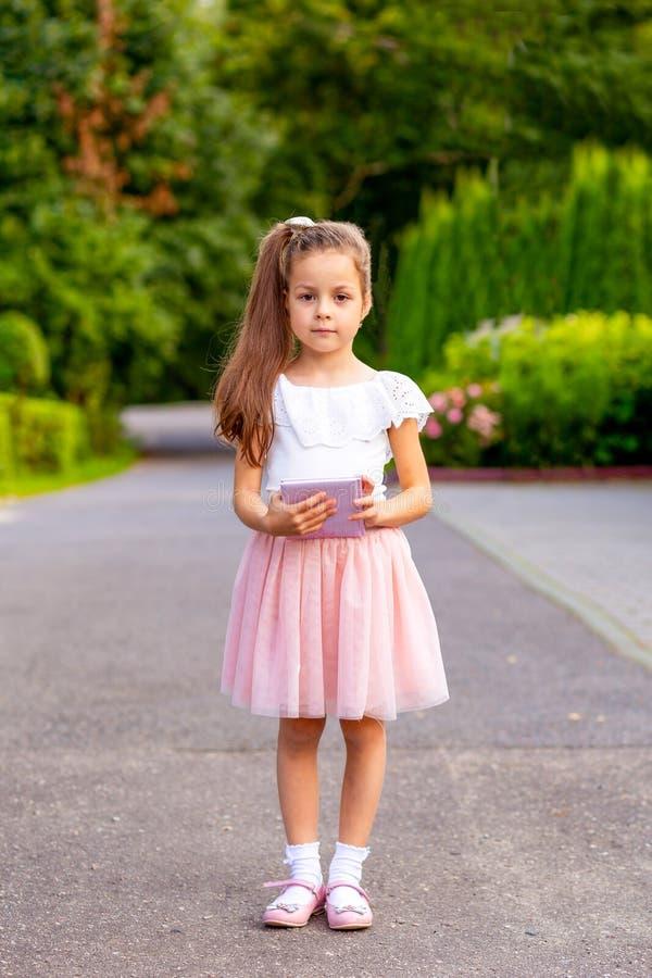 小女孩在她的手上拿着一本书户外 垂直 库存图片