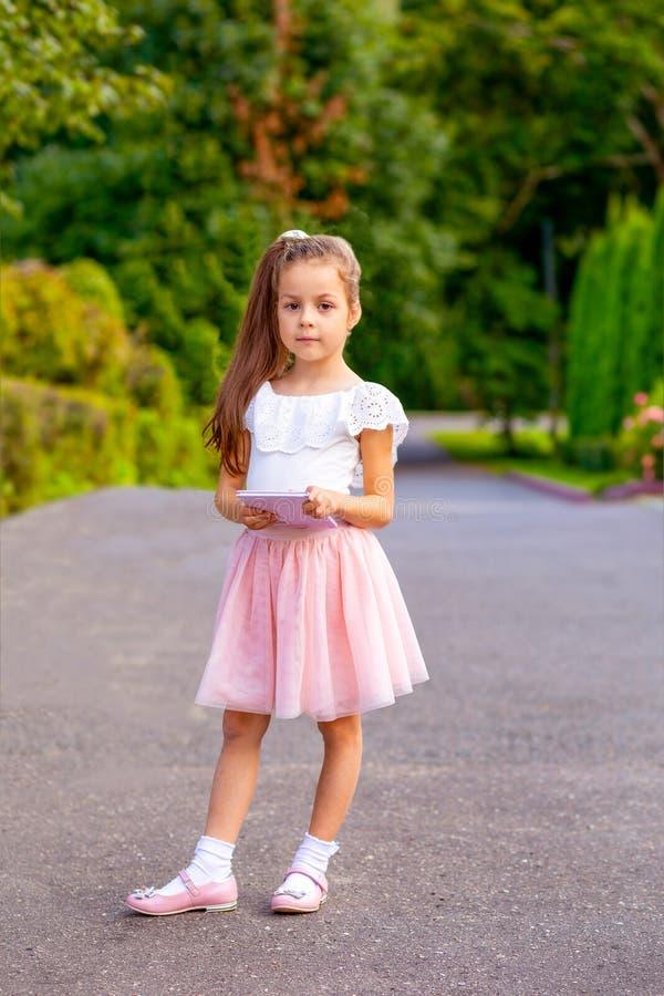 小女孩在她的手上拿着一本书 垂直 库存照片