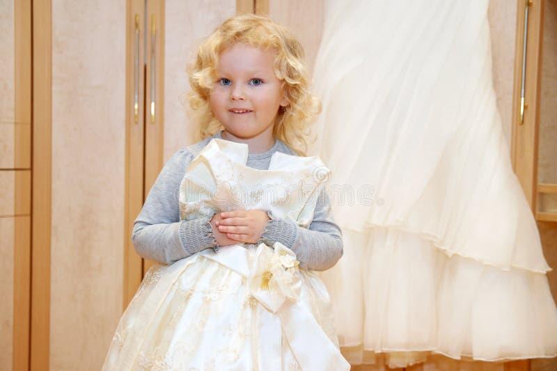 小女孩在婚礼礼服享用在她的母亲` s新娘` s礼服附近 库存图片