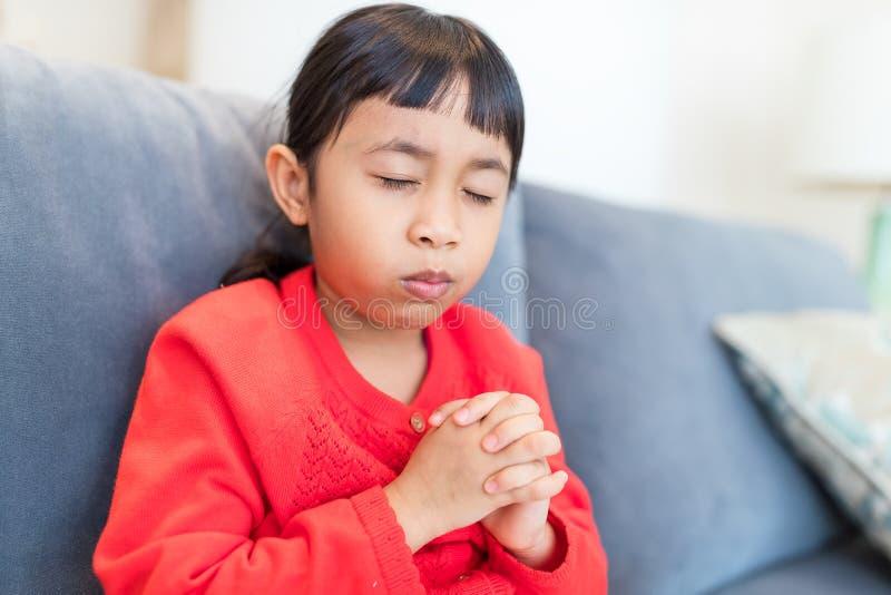 小女孩在家祈祷 免版税库存图片