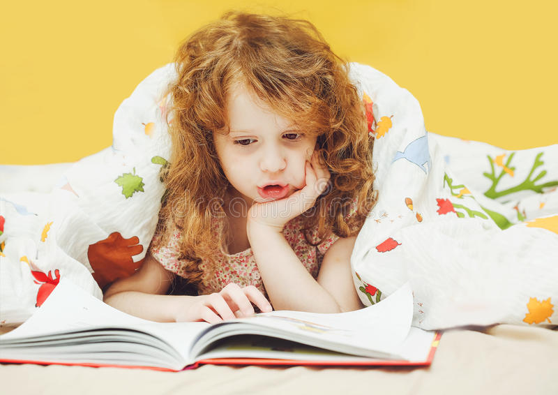 小女孩在床上的读一本书在去前睡 被定调子的i 库存照片