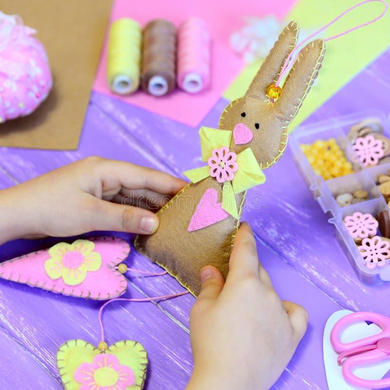 小女孩在手上拿着一个毛毡复活节兔子玩具 女孩显示与心脏的一个毛毡兔宝宝 手工制造复活节礼物 免版税图库摄影