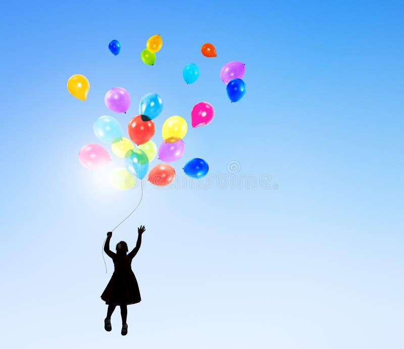小女孩在拿着气球的天空中图片
