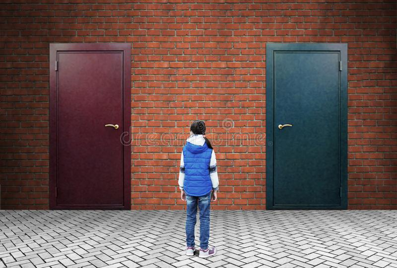 小女孩在有两个被关闭的门的一个砖墙前面站立,不用板材 免版税库存图片