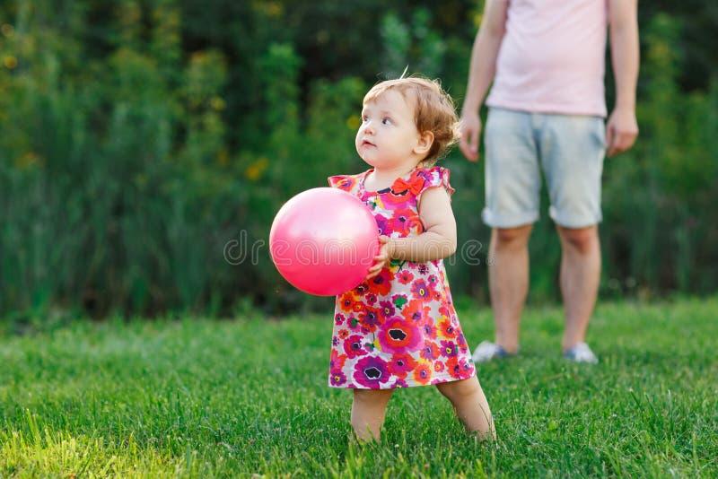 小女孩在有球的公园在手上 免版税库存图片
