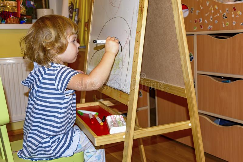 小女孩在有色的标志的委员会画 免版税库存照片