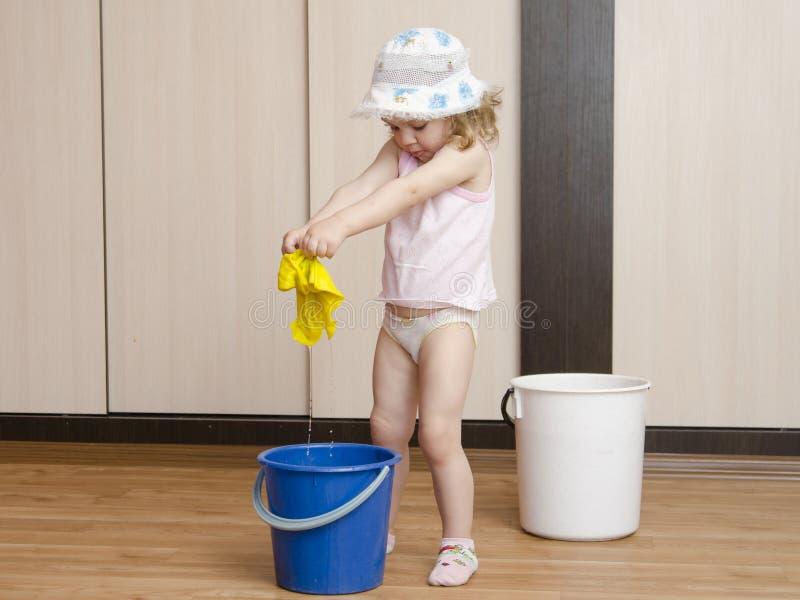 小女孩在桶的洗涤旧布 免版税图库摄影