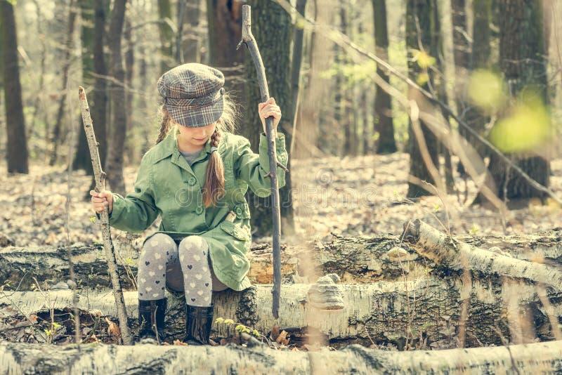 小女孩在森林坐树桩 库存照片