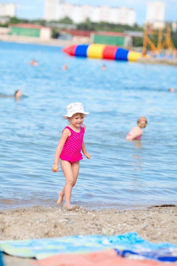 小女孩在海滩去,在海附近 库存图片