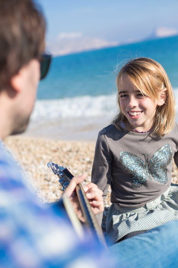 小女孩在海滩的唱歌歌曲画象  免版税库存图片