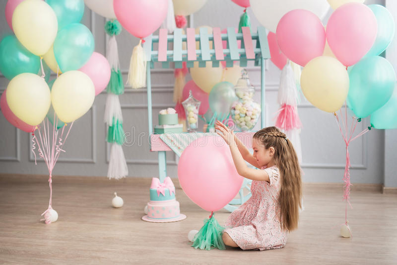 小女孩在演播室装饰的五颜六色的baloons坐 免版税库存图片