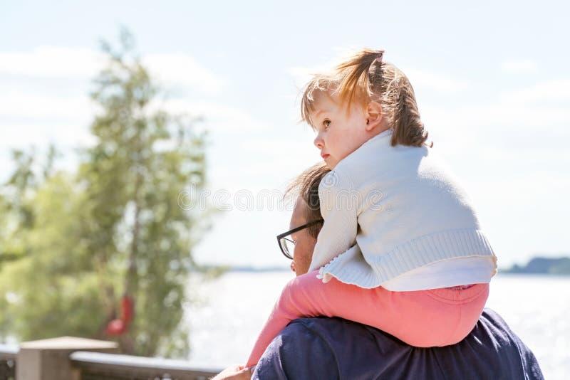 小女孩在爸爸坐脖子 免版税库存照片