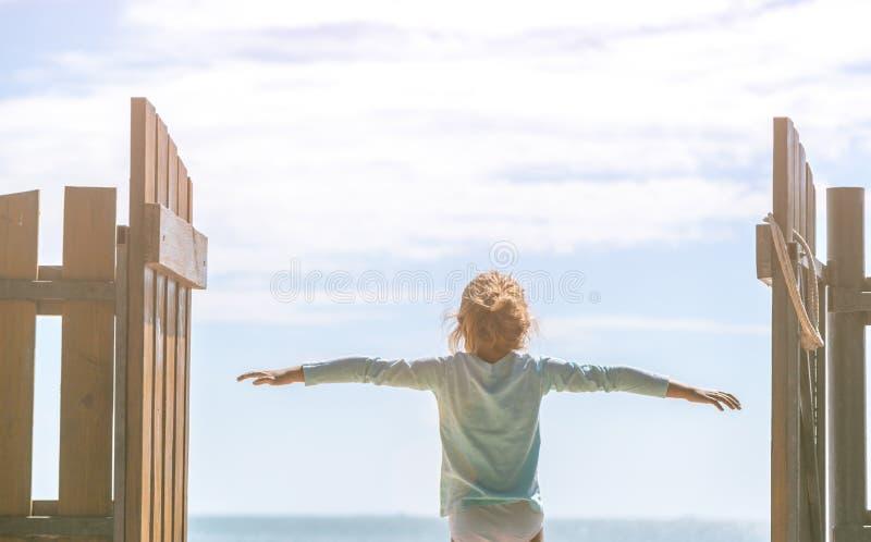 小女孩在蓝天的背景看  免版税库存图片
