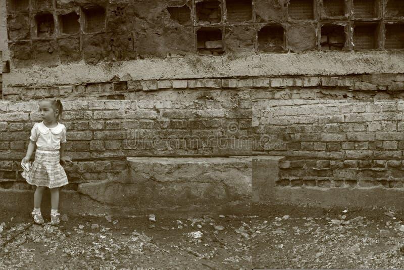 小女孩在被毁坏的墙壁附近站立 库存图片