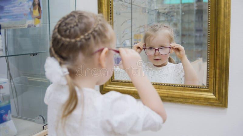 小女孩在镜子-在眼科学诊所的购物附近尝试新的玻璃 免版税库存照片