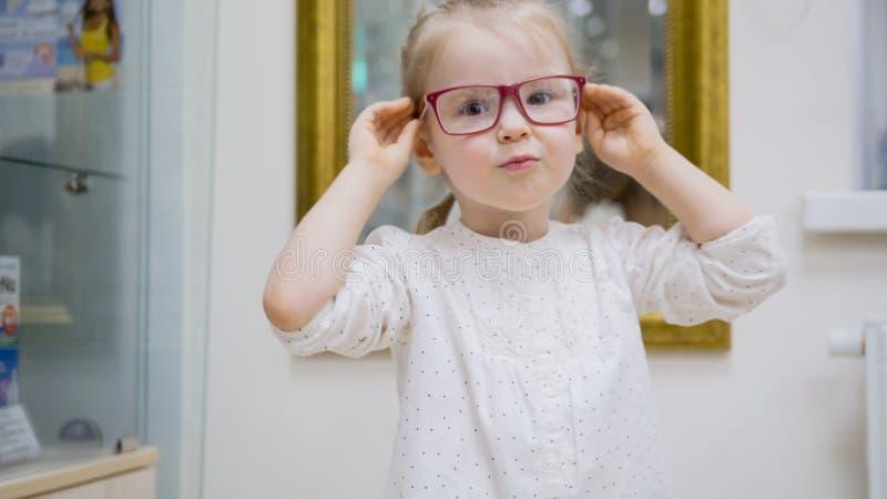小女孩在镜子-在眼科学诊所的购物附近尝试时尚医疗玻璃 免版税库存照片