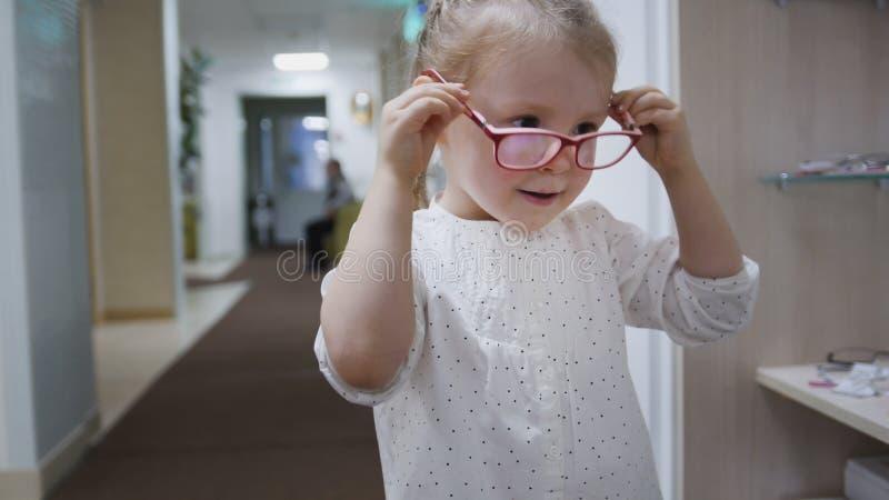 小女孩在镜子-在眼科学诊所的购物附近尝试时尚医疗玻璃 免版税库存图片