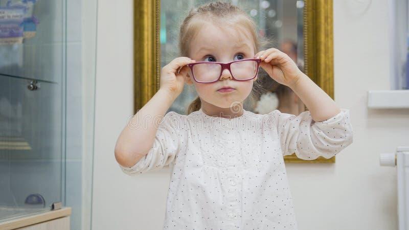 小女孩在镜子-在眼科学诊所的购物附近尝试时尚医疗玻璃 库存照片