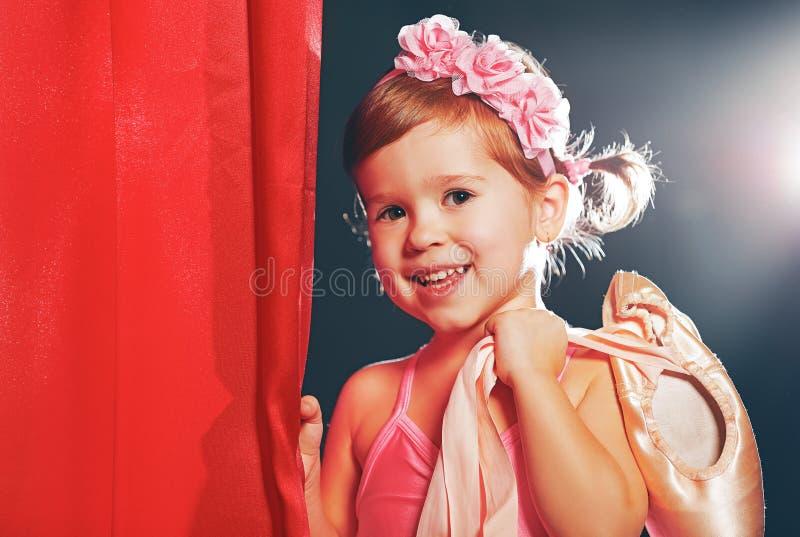小女孩在阶段的芭蕾舞女演员跳芭蕾舞者在红色旁边场面 免版税库存照片