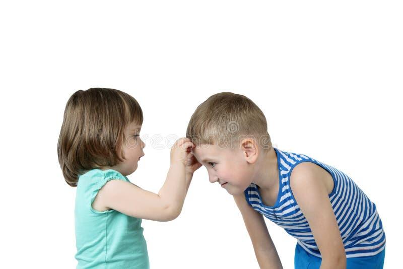 小女孩在更旧的男孩前额黏附补丁 免版税库存照片