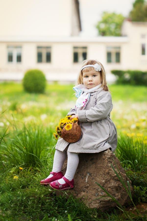 小女孩坐与蒲公英花束的一块石头  免版税库存图片