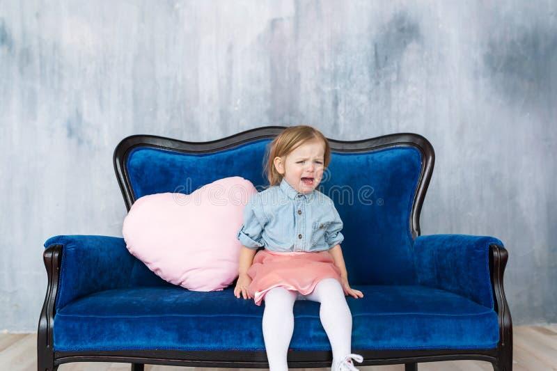 小女孩坐在家哭泣在客厅的沙发 免版税库存照片