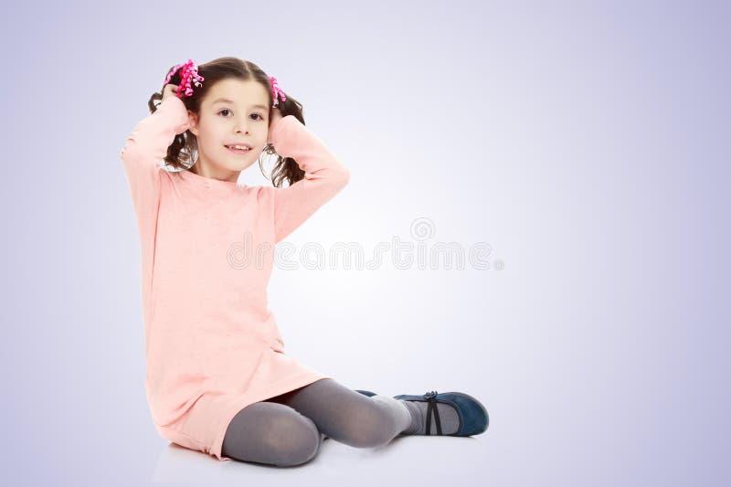 小女孩坐地板和调直头发 免版税库存图片