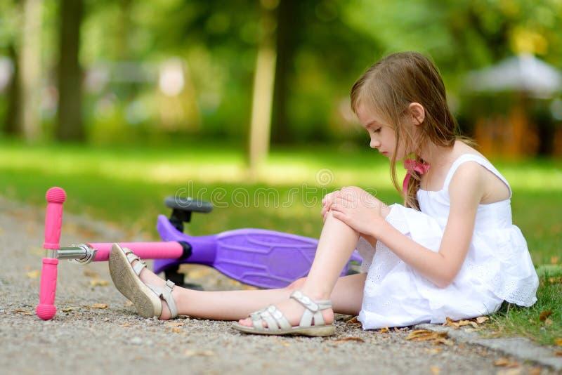 小女孩坐地面,在她跌倒了后,当乘坐她的滑行车时 图库摄影
