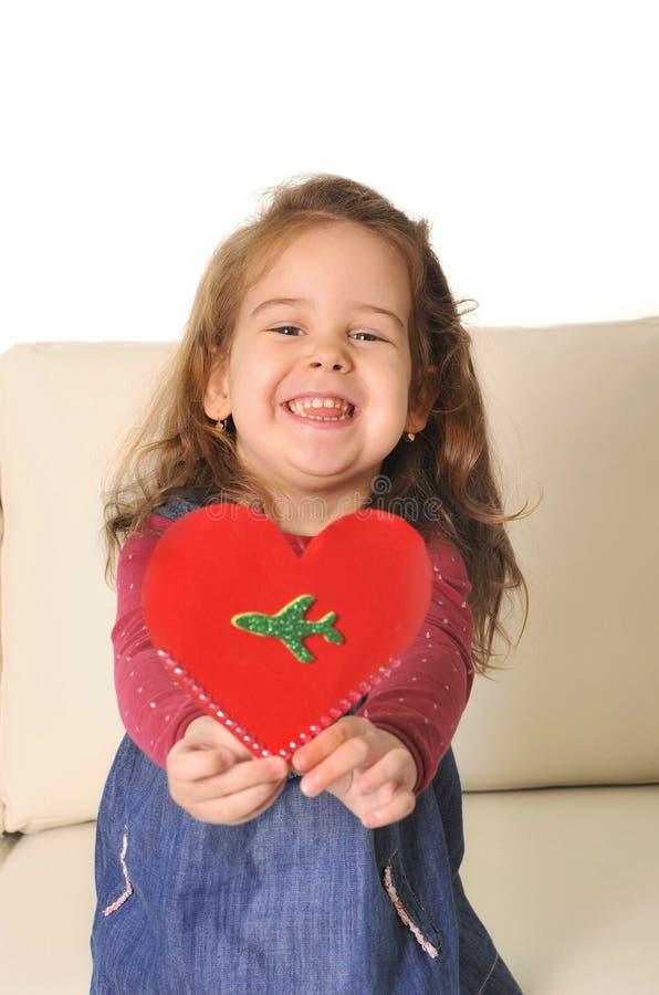 小女孩坐拿着与飞机的长沙发红色心脏形状纸板 库存照片