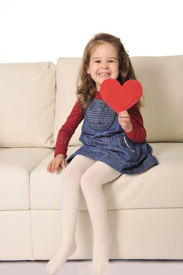 小女孩坐拿着红色心脏形状纸板裁减的长沙发 库存图片