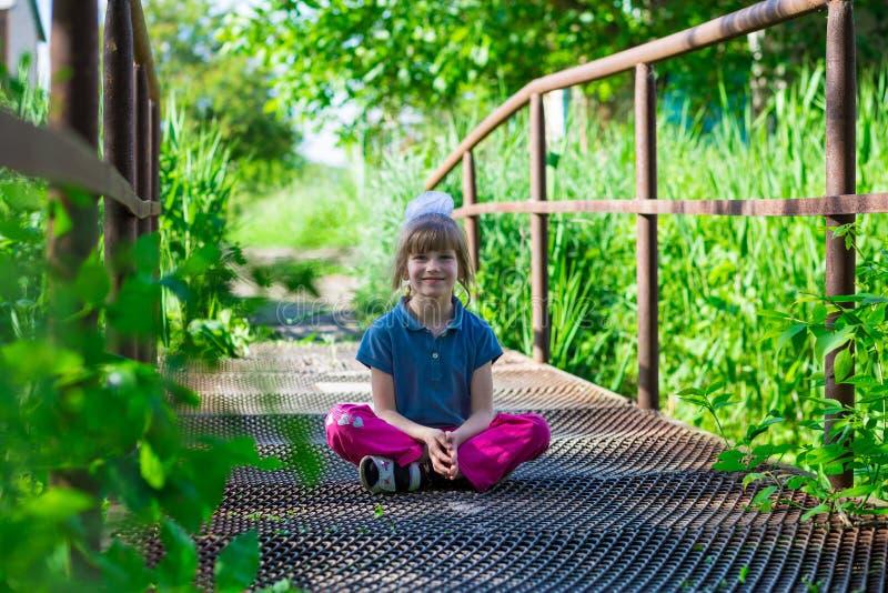 小女孩坐桥梁 库存照片