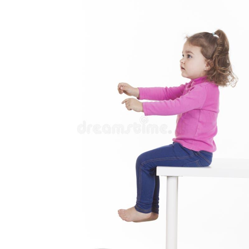 小女孩坐椅子反对白色背景 免版税库存照片