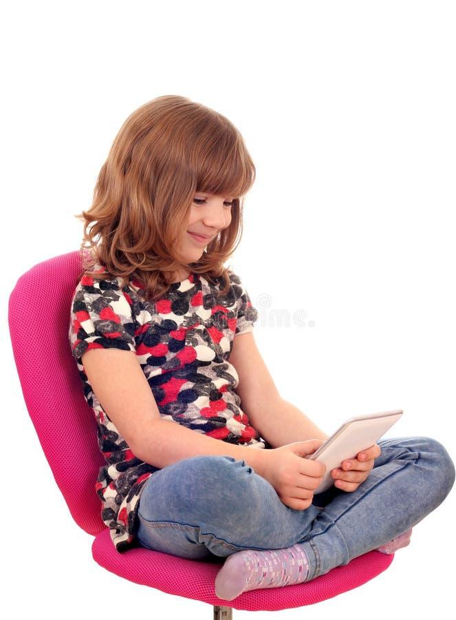 小女孩坐椅子和戏剧与片剂个人计算机 免版税图库摄影