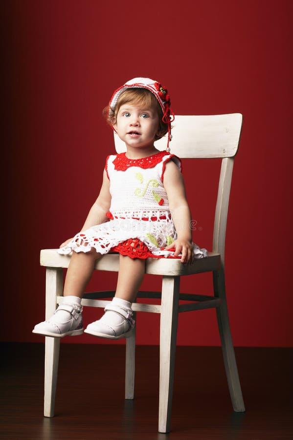 小女孩坐椅子 免版税库存图片