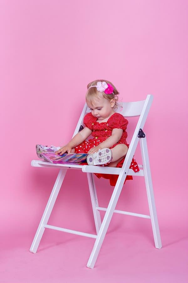 小女孩坐椅子ang阅读书 库存图片
