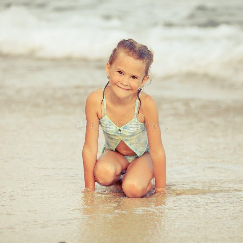 小女孩坐海滩 免版税库存照片