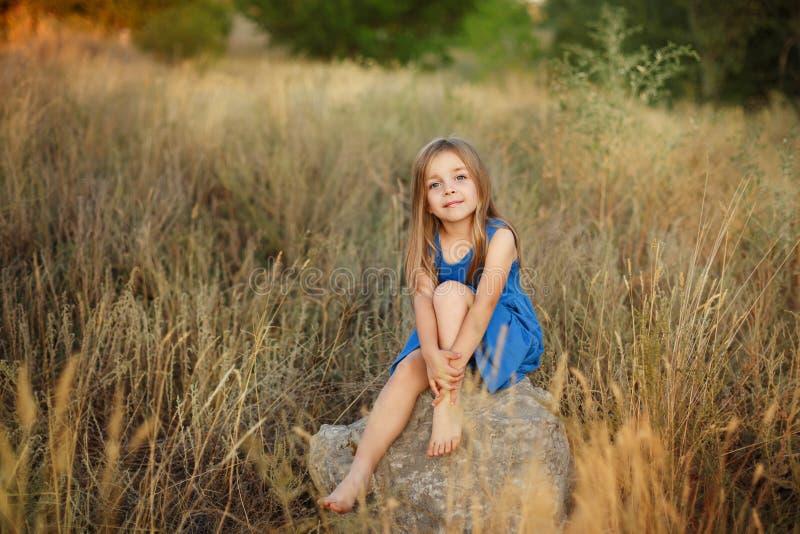 小女孩坐石头 免版税图库摄影